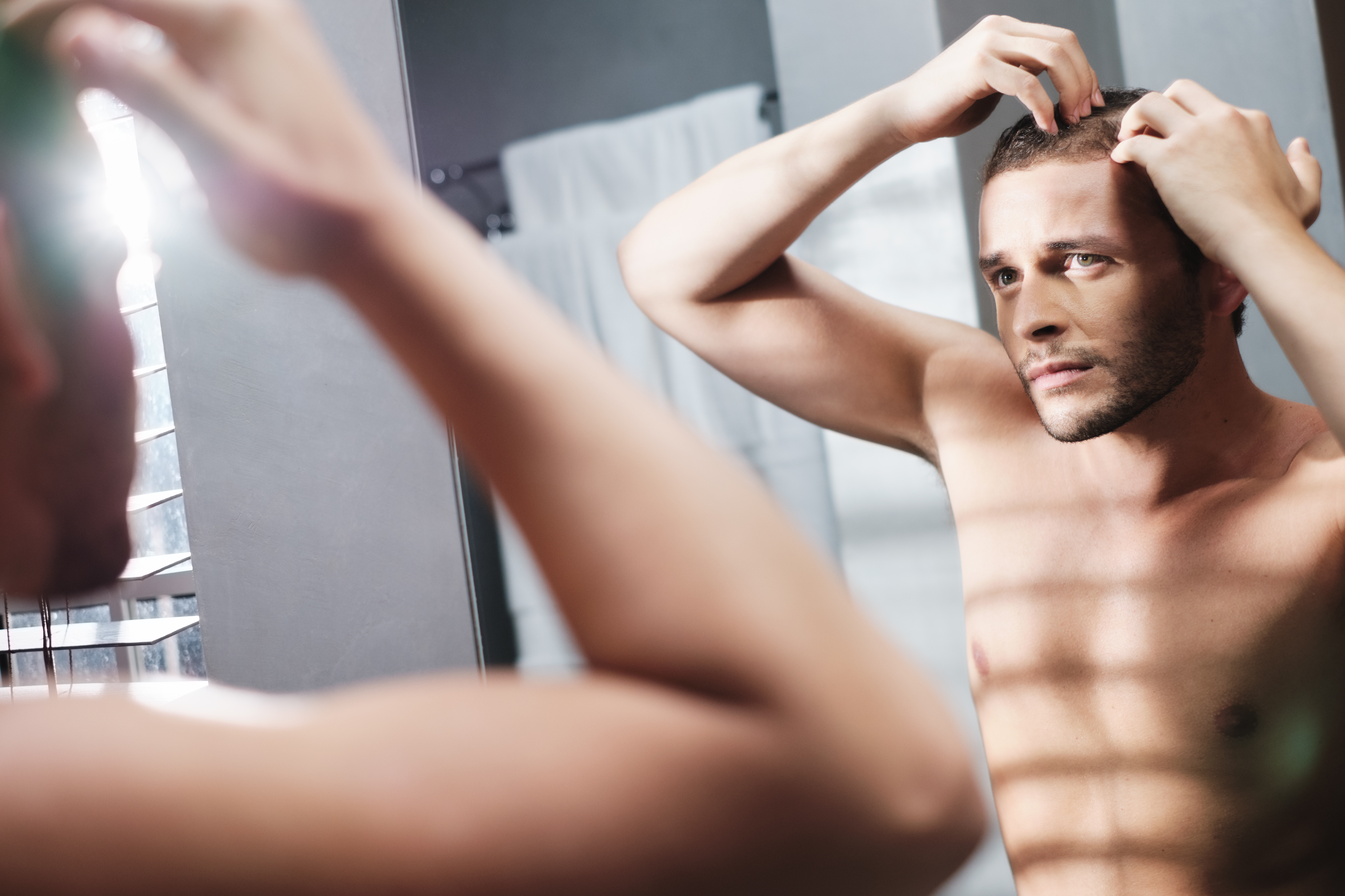 A Man stand in front of a mirror concerned about his hair loss